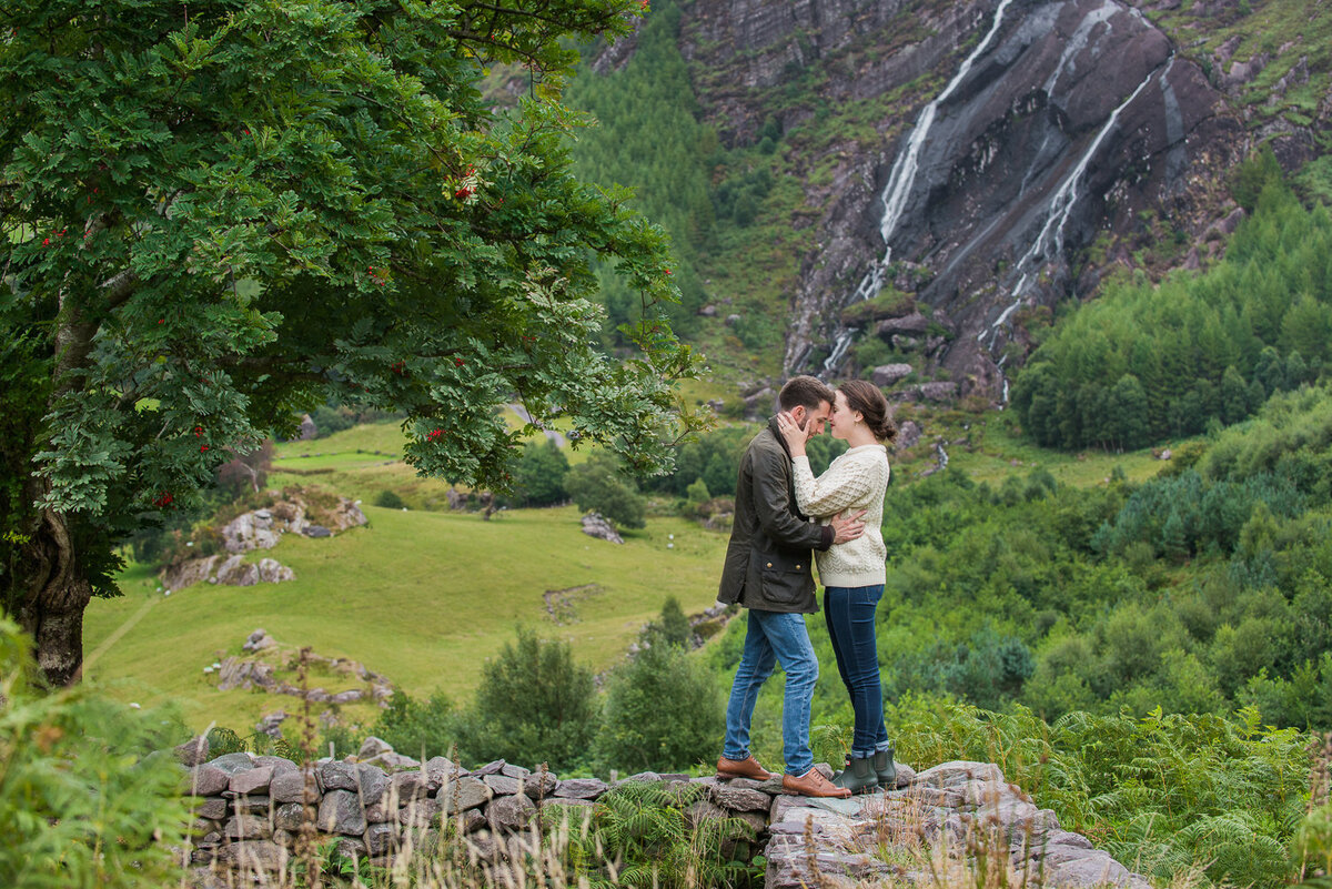 Young couple standing on an old, stone wall kissing in front of a waterfall surrounded by trees