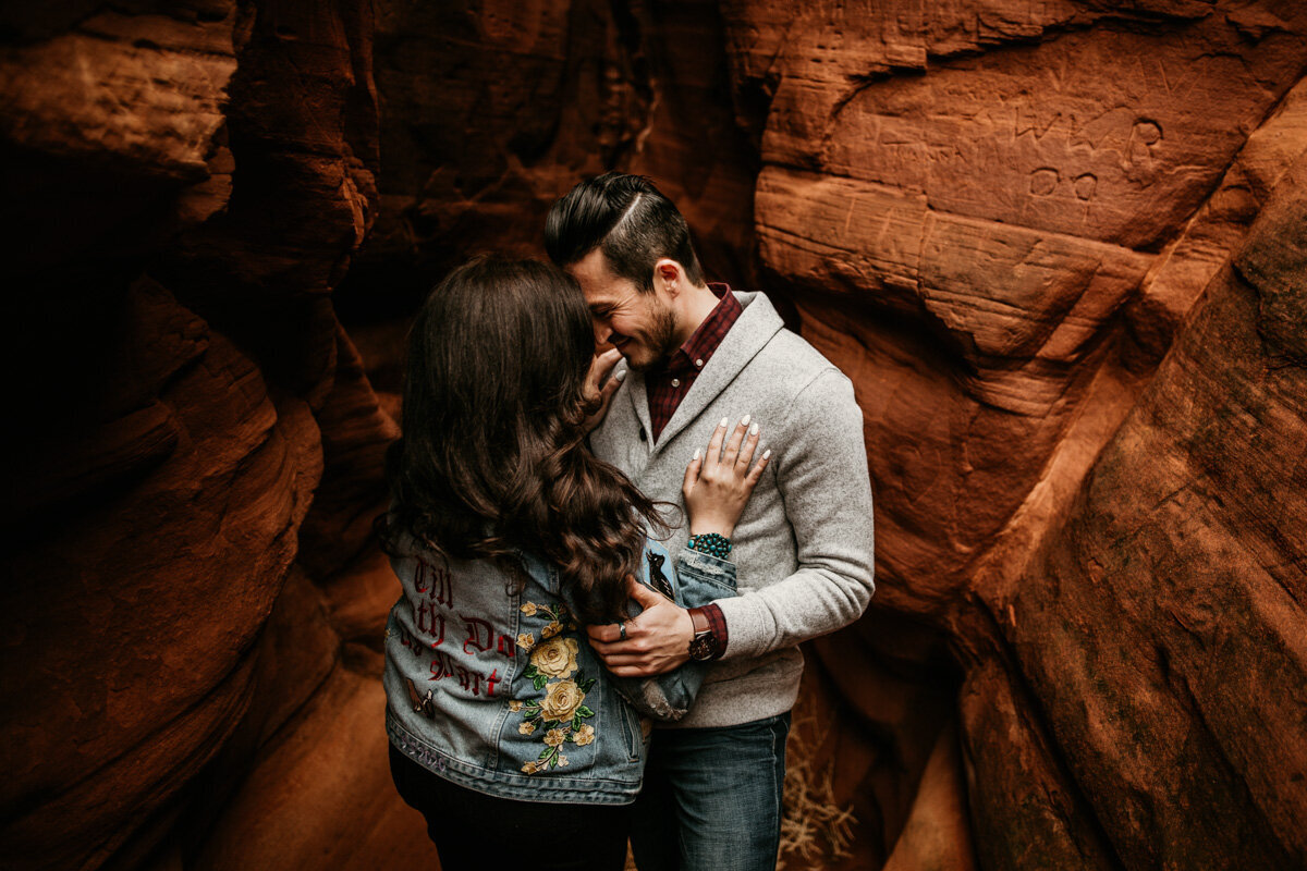 man and woman holding each other in red rock canyon