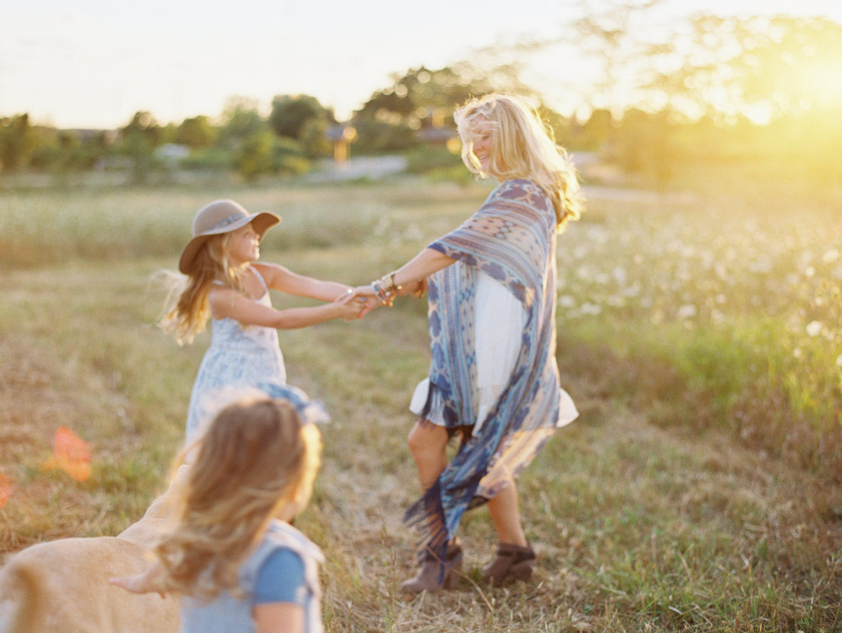 mom dancing with daughters at sunset