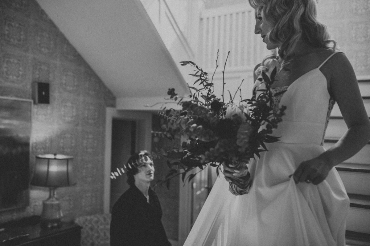 Wedding Photographer, black and white of bride walking down the stairs looking at groom