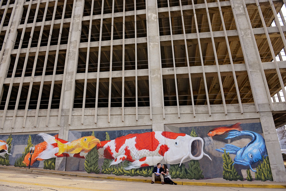 Couple cuddling by mural for downtown Huntsville engagement