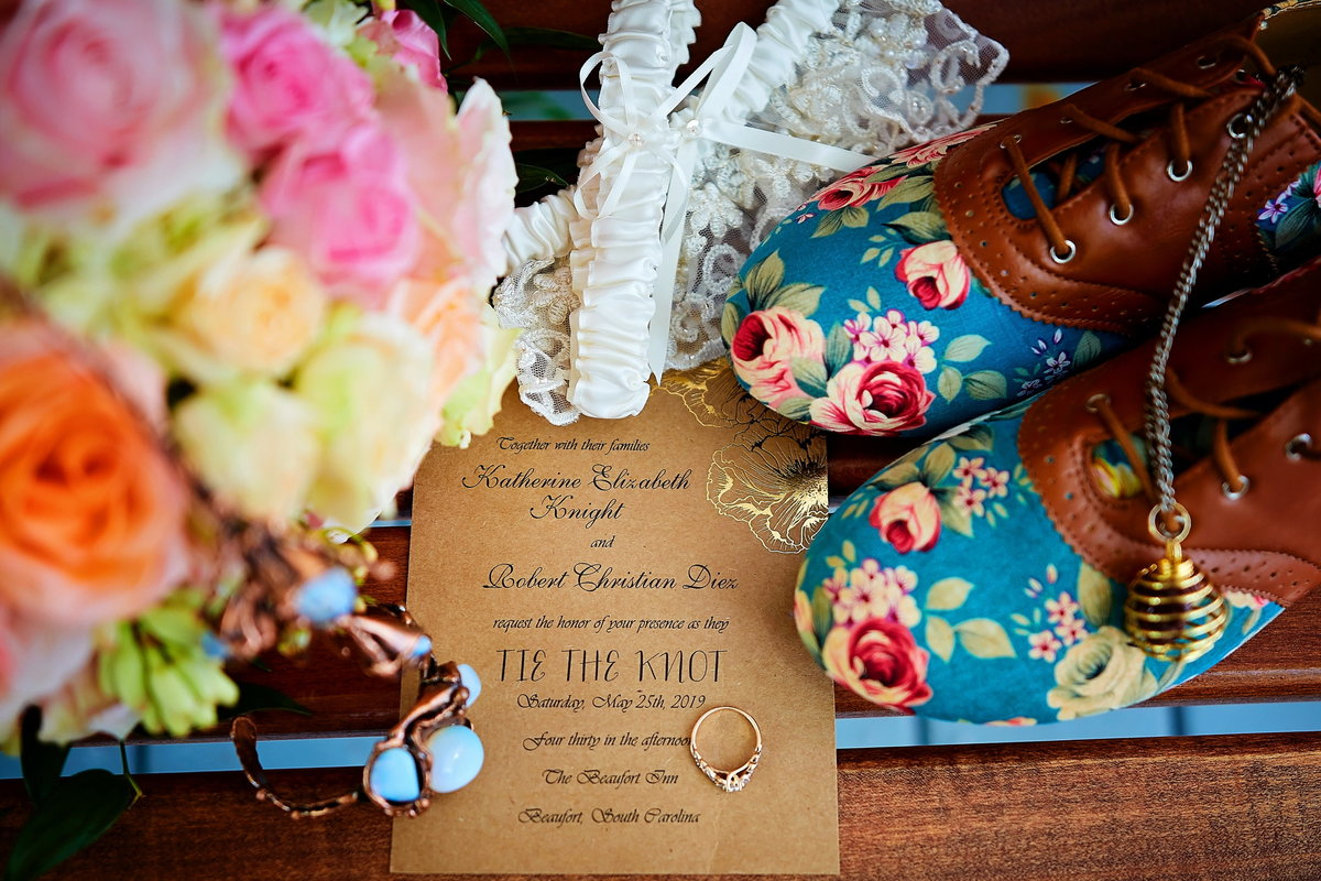 Colorful, offbeat bridal flatlay, with floral shoes, gold invitation, rose gold wedding band, colorful pink rose bouquet, and wire turquoise necklace