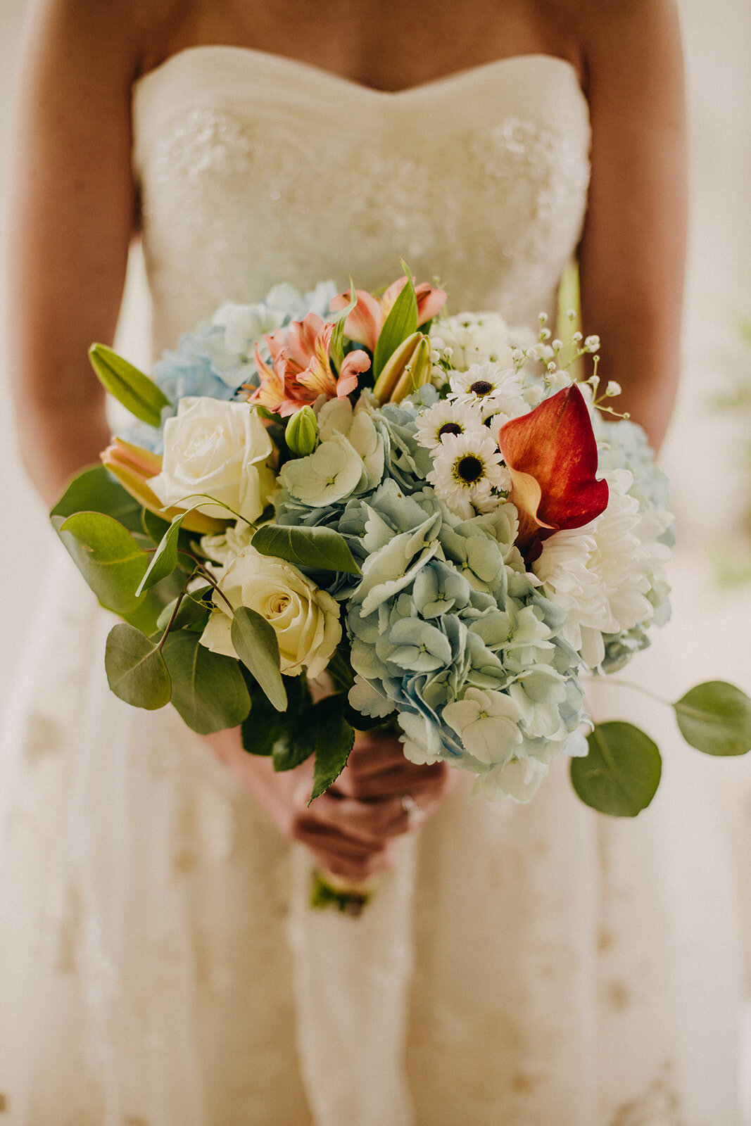 bride wearing strapless gown holds bouquet blue hydrangeas orchid white roses eucalyptus
