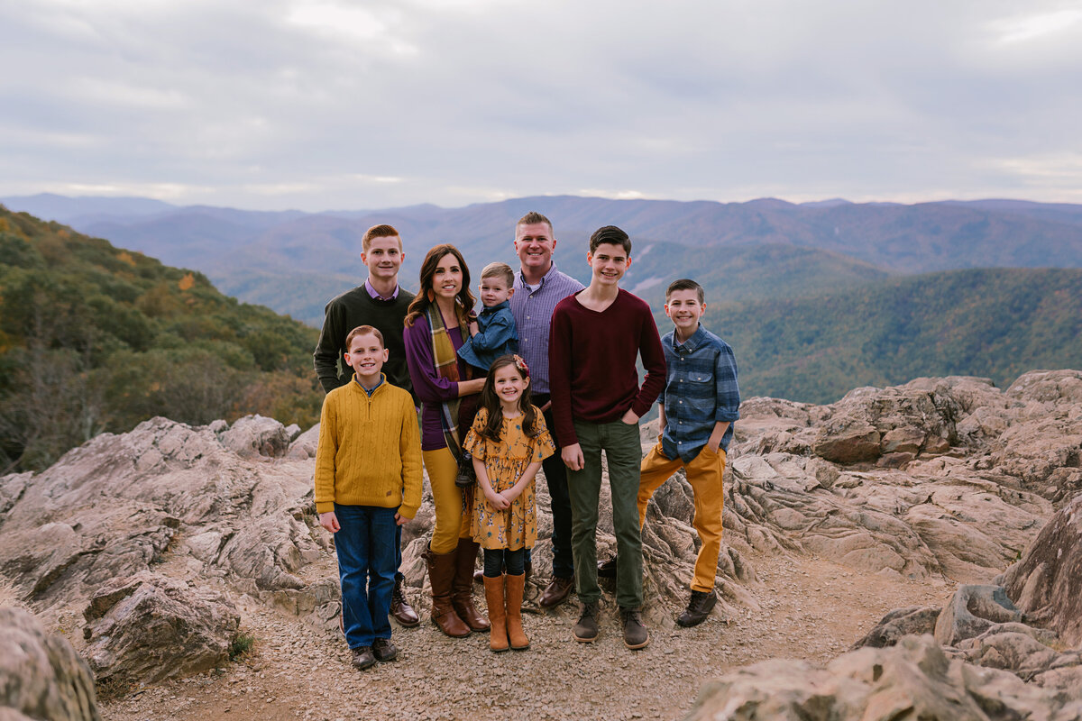 Family Standing on cliff with mountains behind htem