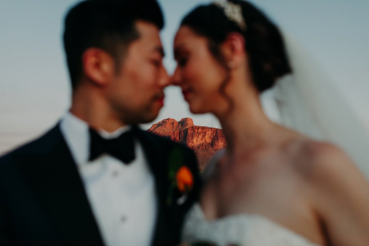 Superstition Mountains peek through the middle of a bride and groom nuzzling noses