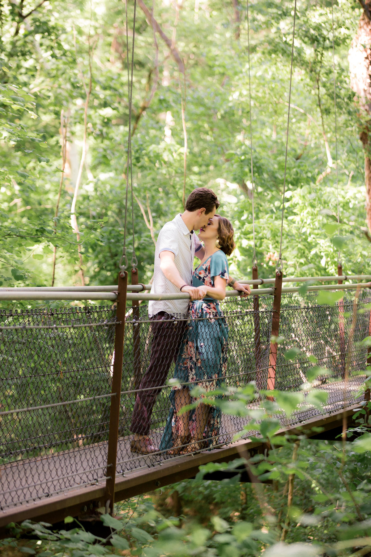 engaged couple kissing on bridge in lullwater park beside emory college in Atlanta