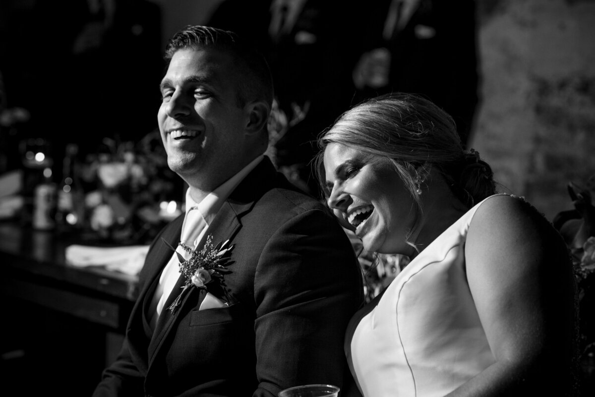 Bride and groom laughing during reception toasts