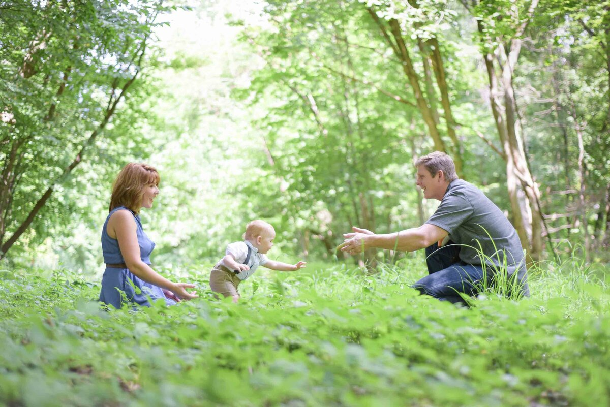 Family outside in a forest with a toddler taking their first steps
