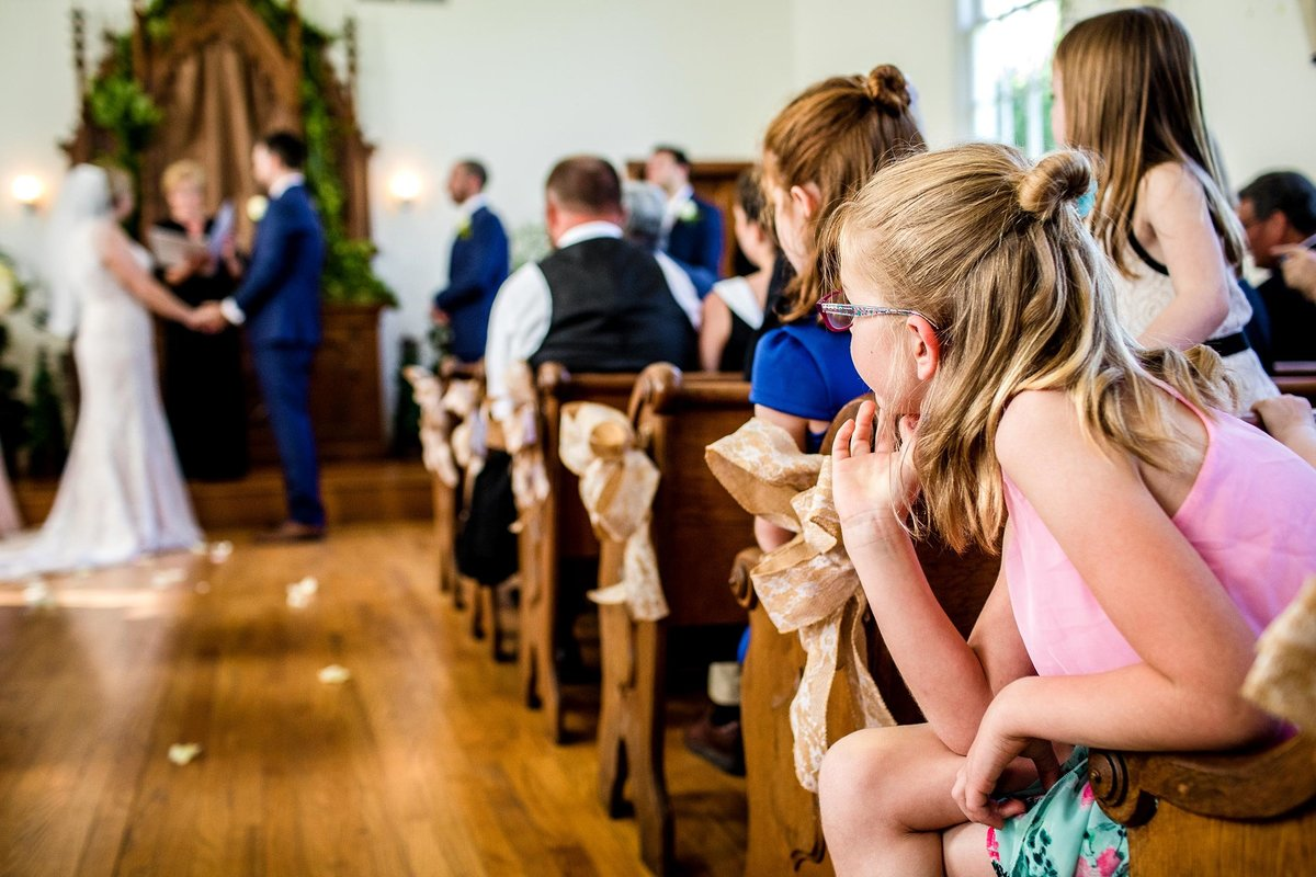 A guest watches a wedding ceremony during an Oak Hill Farm wedding.