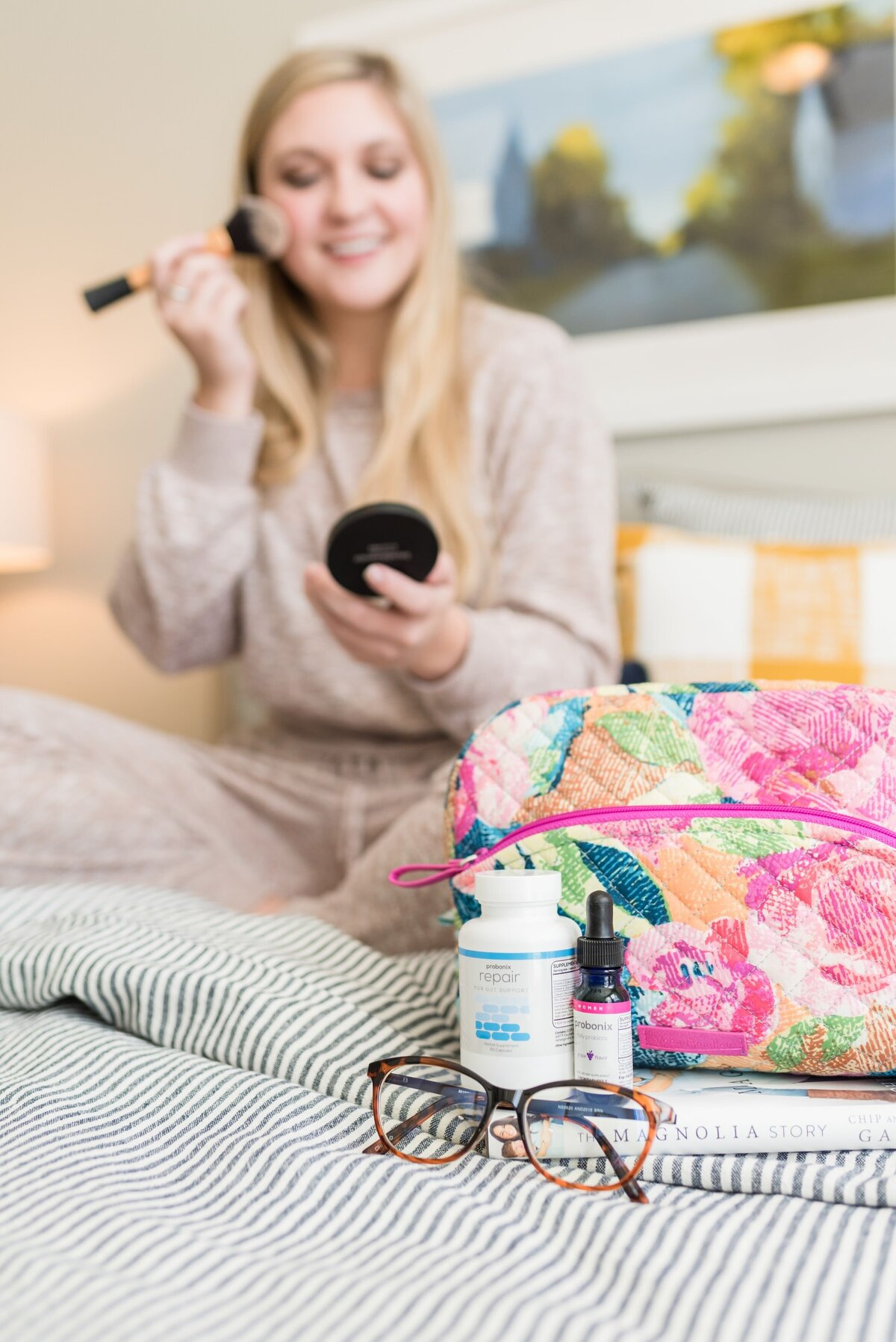 Product photo of Humarian probiotics with a make up bag and glasses and a woman blurry in the background apply makeup