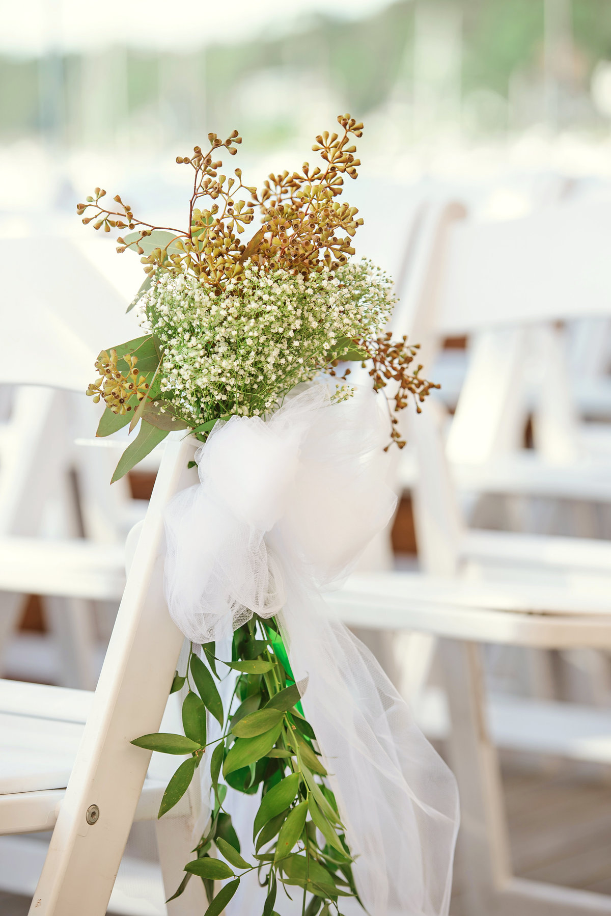 Baby breath flowers placed on chairs for wedding ceremony