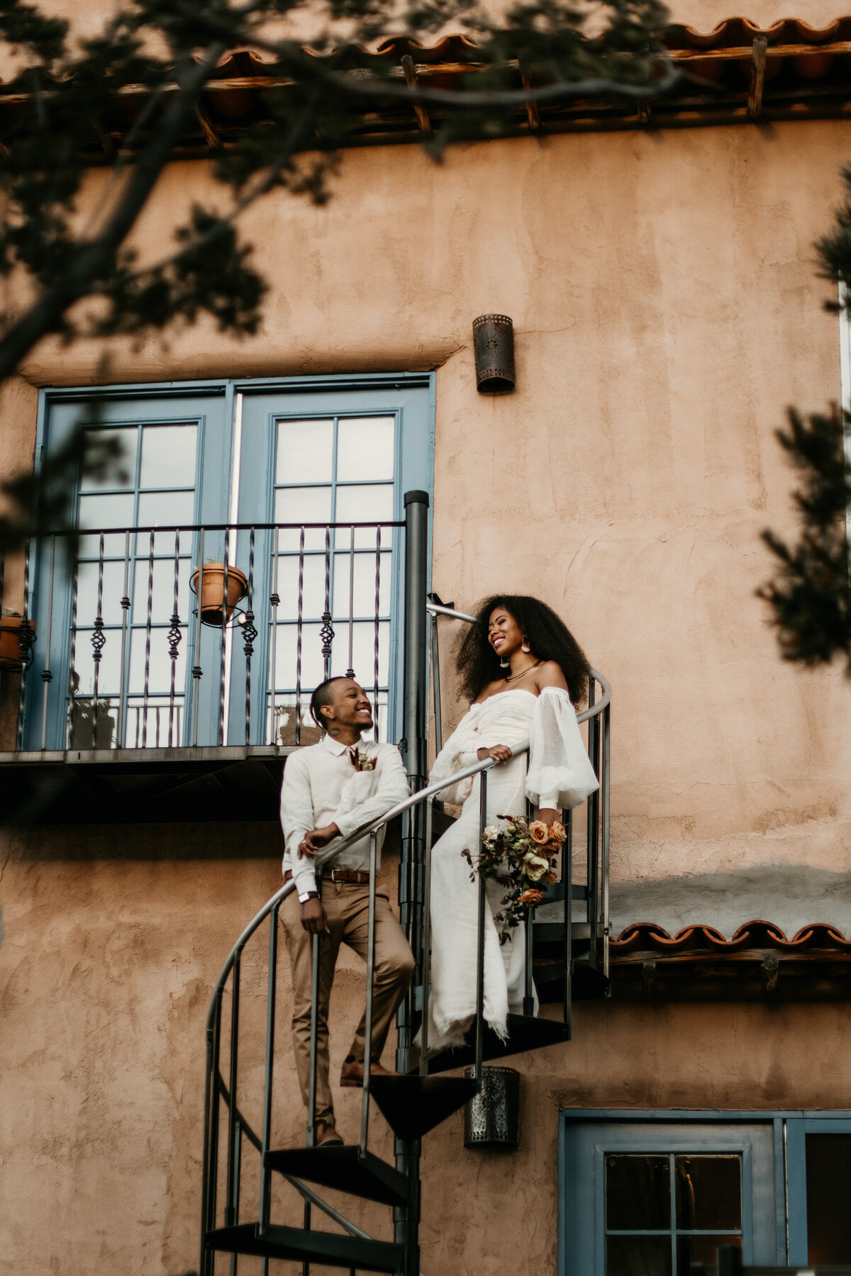 Bride and groom standing on a spiral staircase in Santa Fe venue