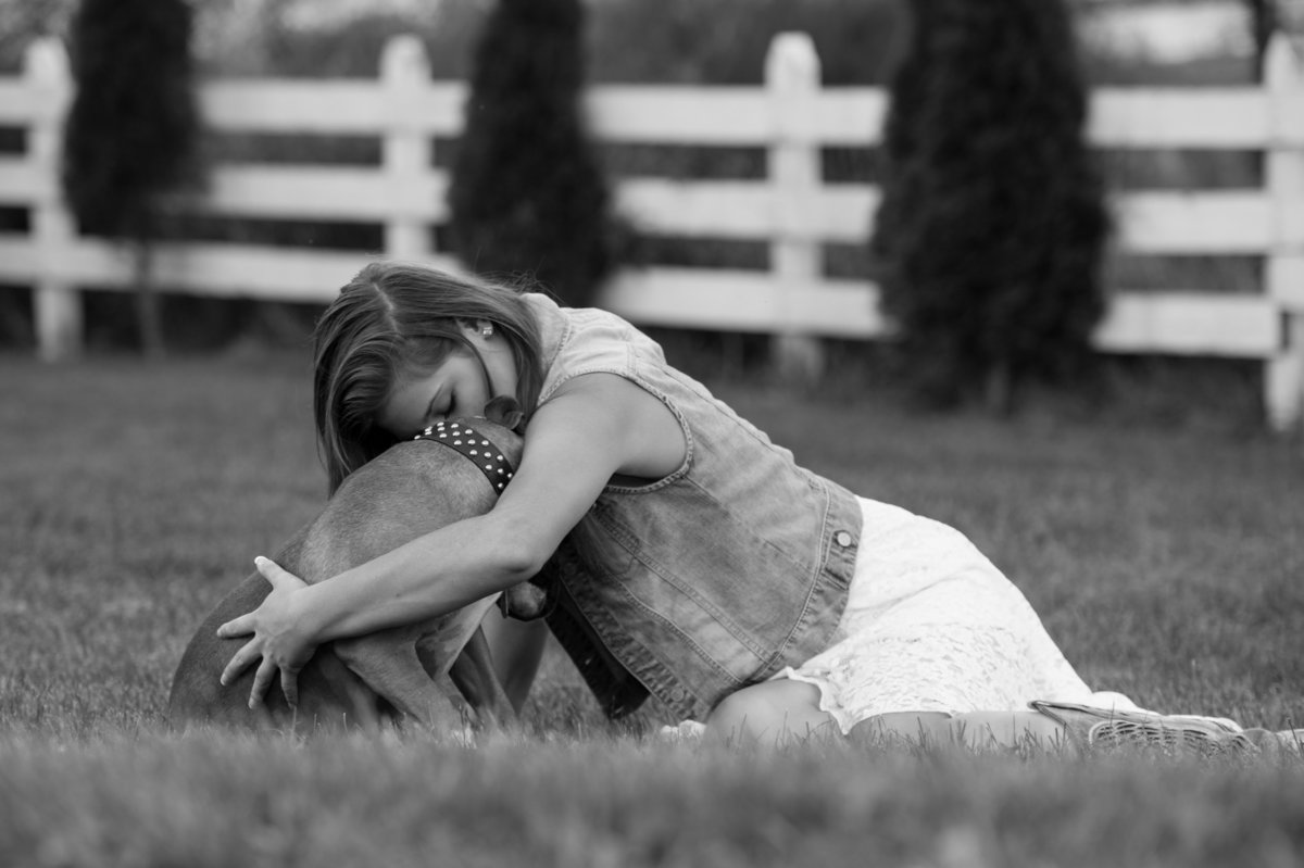 girl hugging dog black and white photo