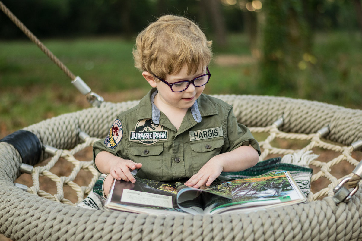 A young boy reads a dinosaur book in a large swing.