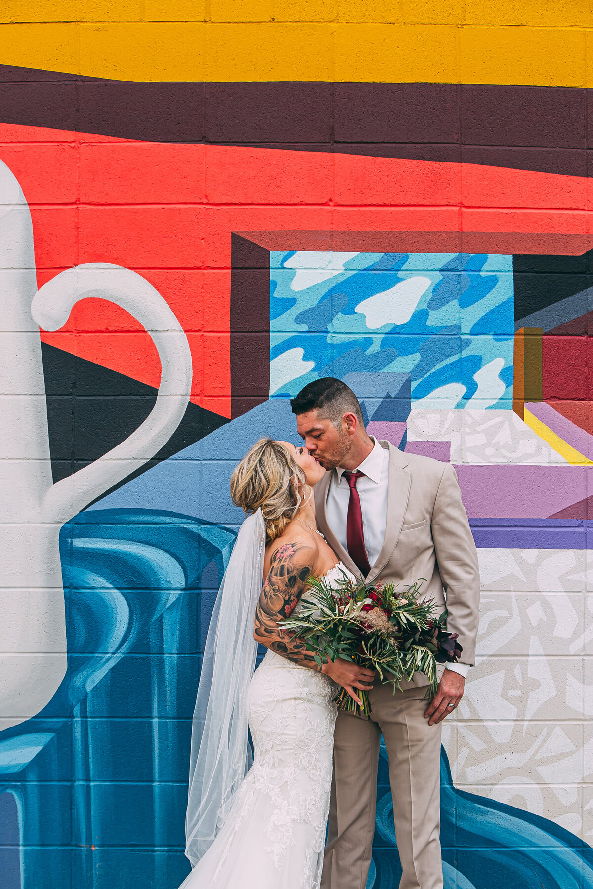 bride and groom share a kiss in front of graffiti wall on their wedding day. Long veil and large bouquet.
