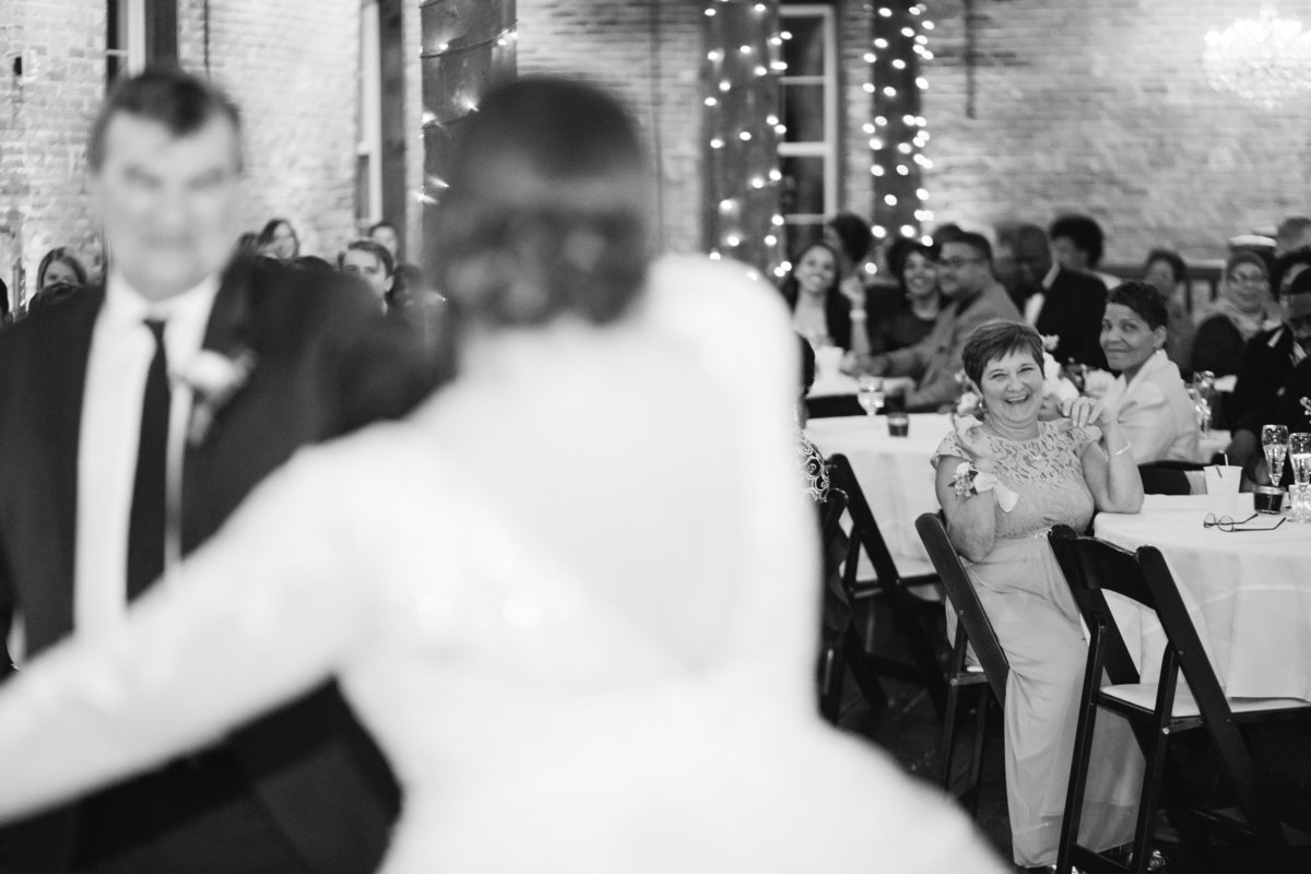 Mother of the bride cheering as her daughter dances with her husband