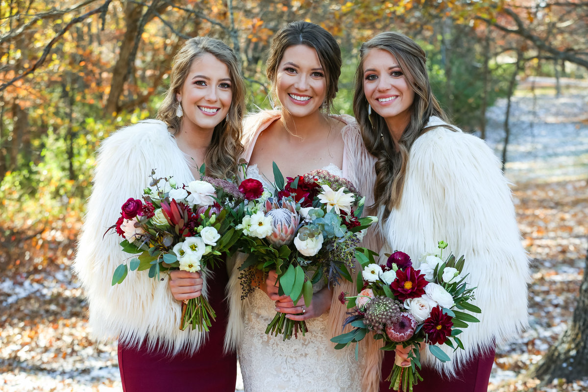 Romantic Fall Elopement  bride and bridesmaids with red wine dresses and fur jackets at Greensfelder County Park  in St. Louis  by Amy Britton Photography Photographer in St. Louis