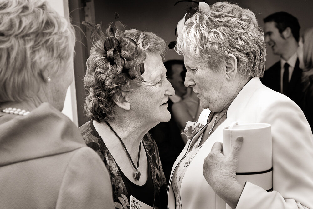 two female wedding guests in their fifties gossiping at a wedding