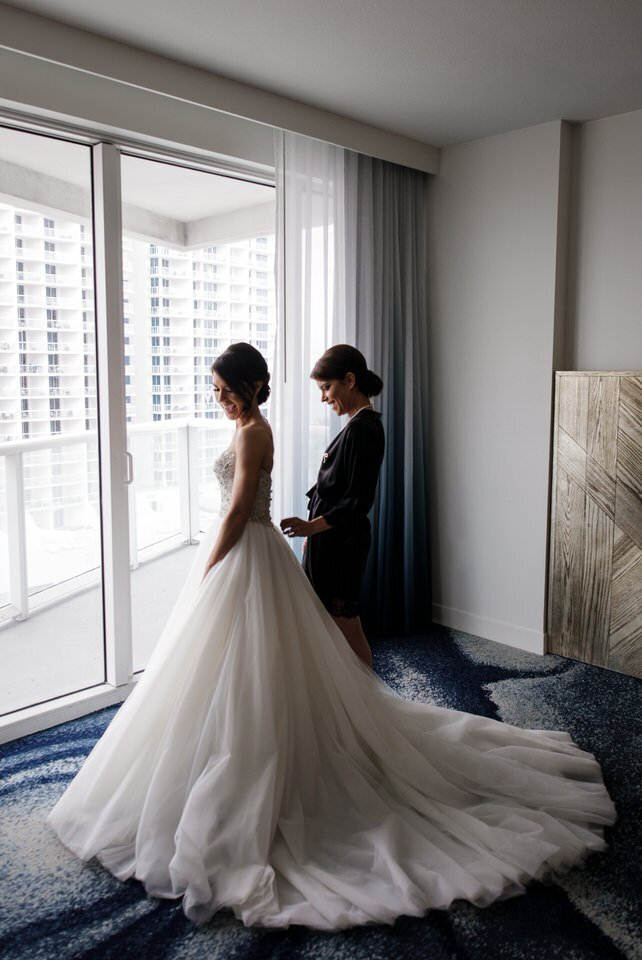 Bride and bridesmaid get ready in the window light of the bridal suite