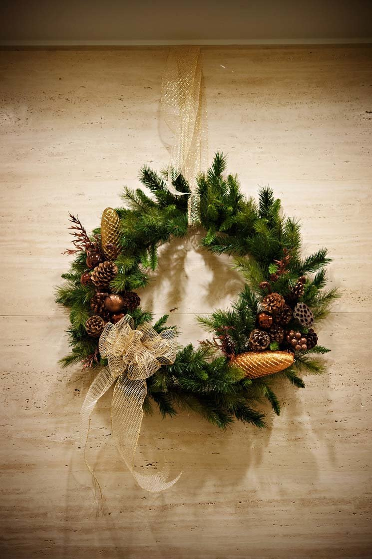 holiday wreath of evergreen, gold acorns, gold sparkle ribbon bow hanging on wall