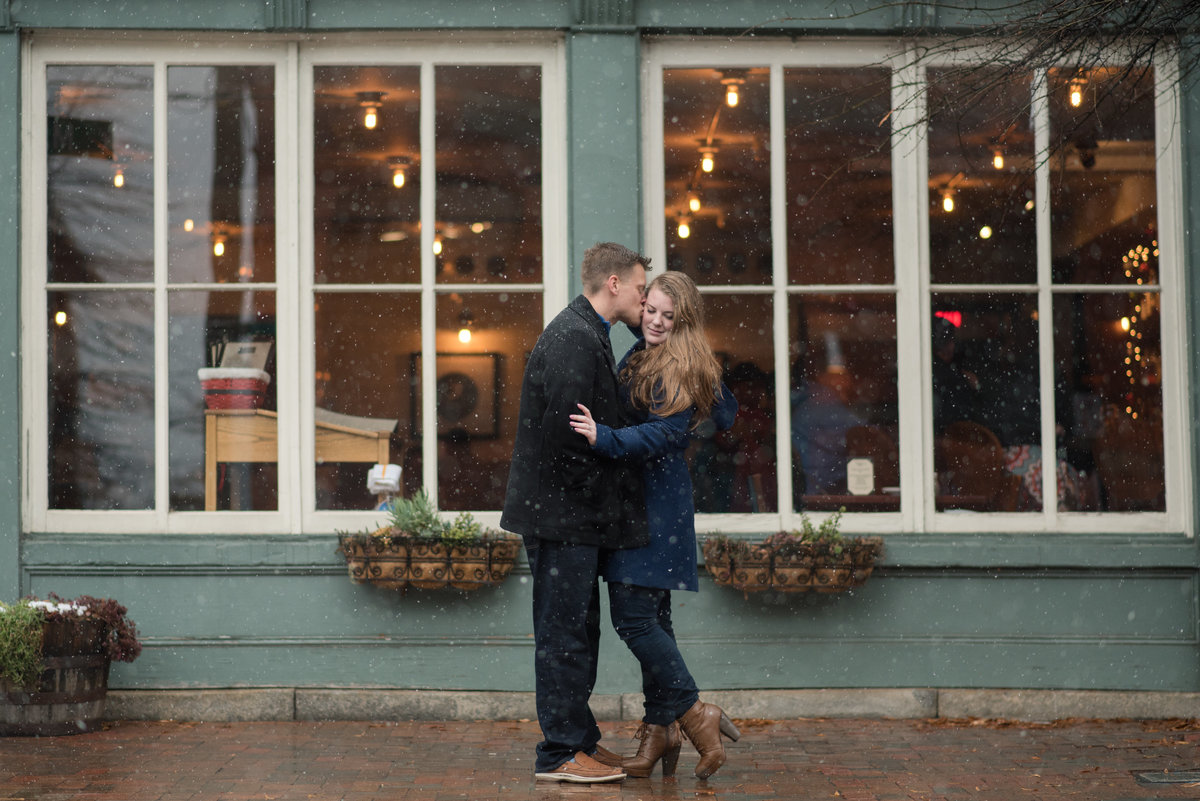 couple kisses in snow outside of downtown richmond bar by rva photographer