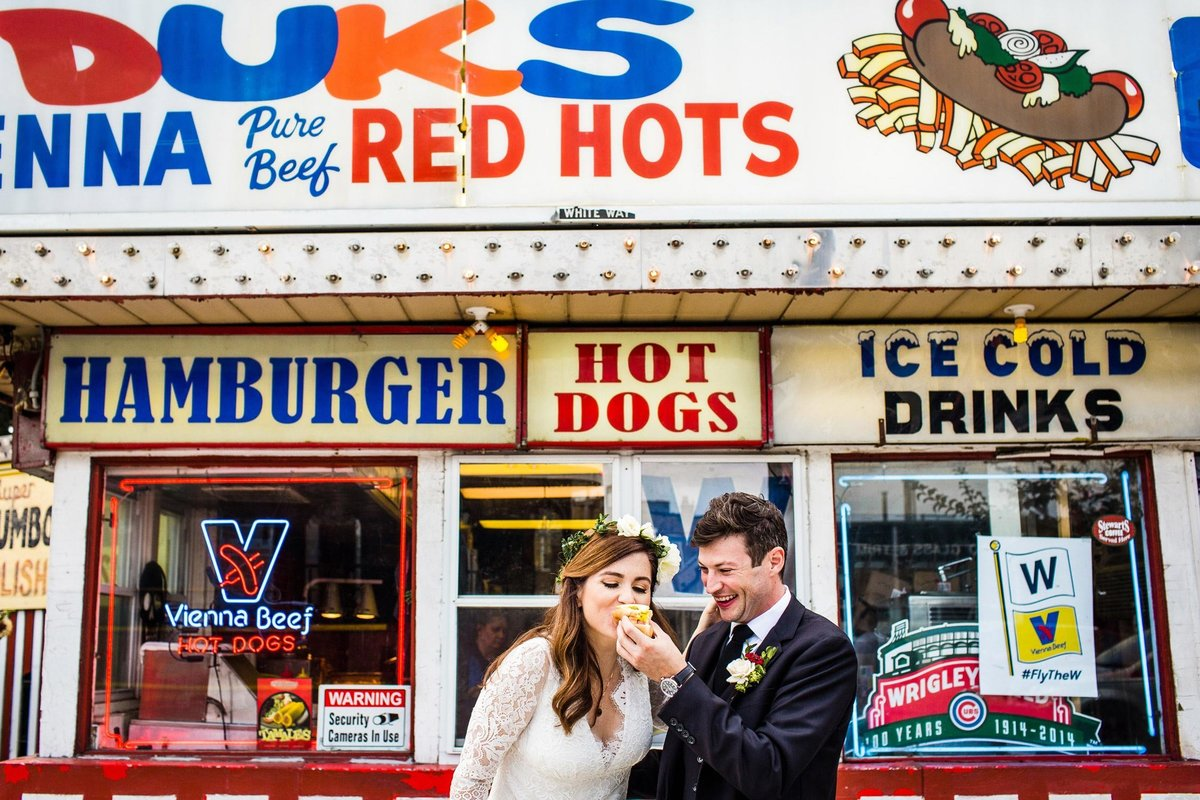 A couple shares a hot dog together at Duks Red Hots in Chicago.