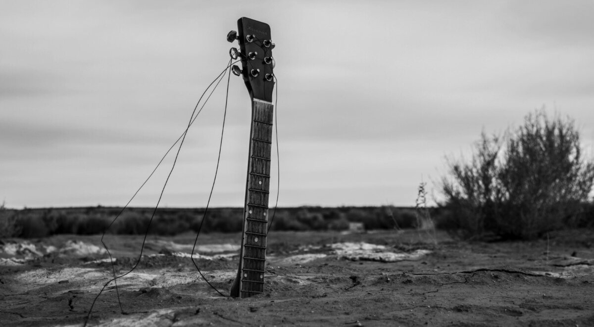 Music Art Photography guitar neck sticking out of stand in desert black and white
