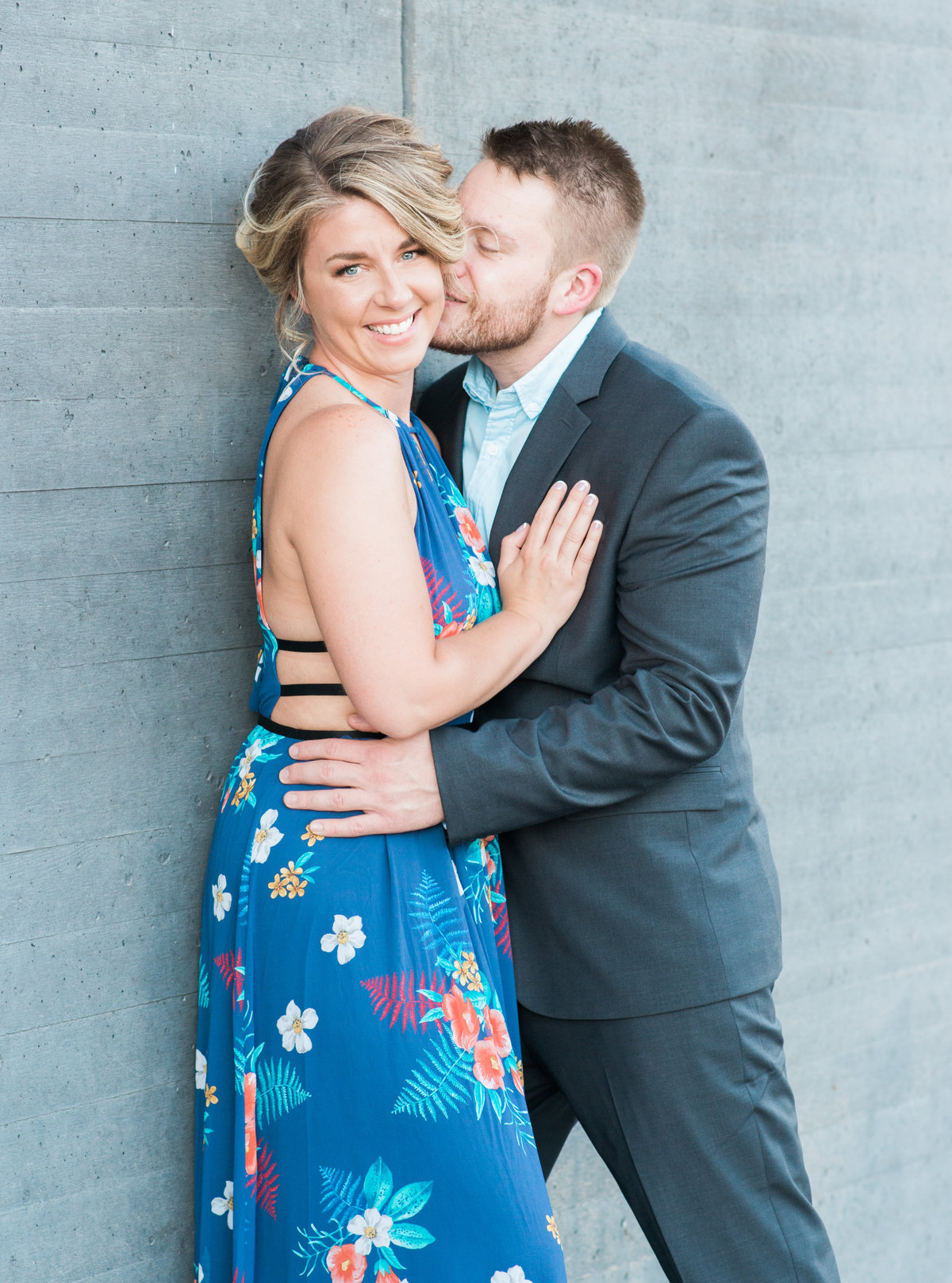 Couple outdoors at the Figge Art Museum in downtown davenport for engagement pictures wearing a blue suit and a dress from Express
