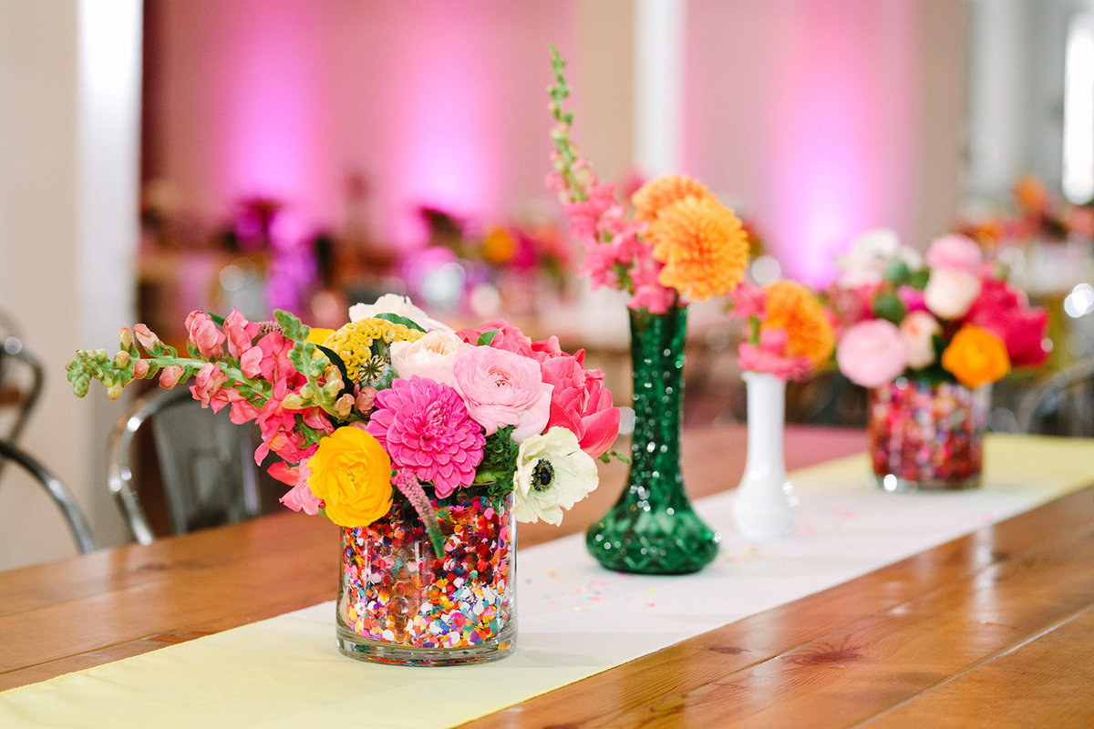 Wedding reception table setting with bright pink and yellow floral centerpieces filled with confetti at The Unique Space LA