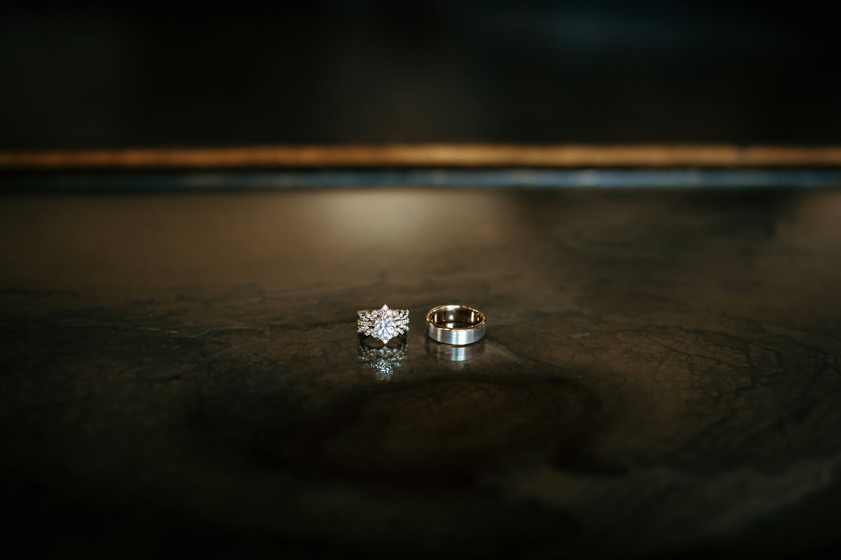 A photograph of a dramatic closeup view of the stunning wedding rings side by side on a dark stone surface by Garry & Stacy Photography Co - St Petersburg wedding photographers