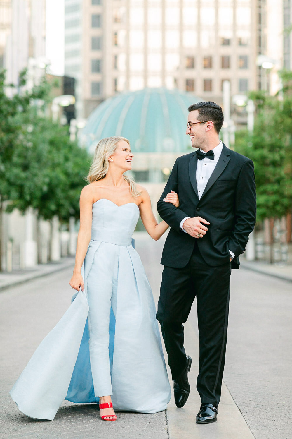 Man in black tuxedo and woman in light blue jumpsuit and red shoes walking side by side in downtown Dallas engagement session
