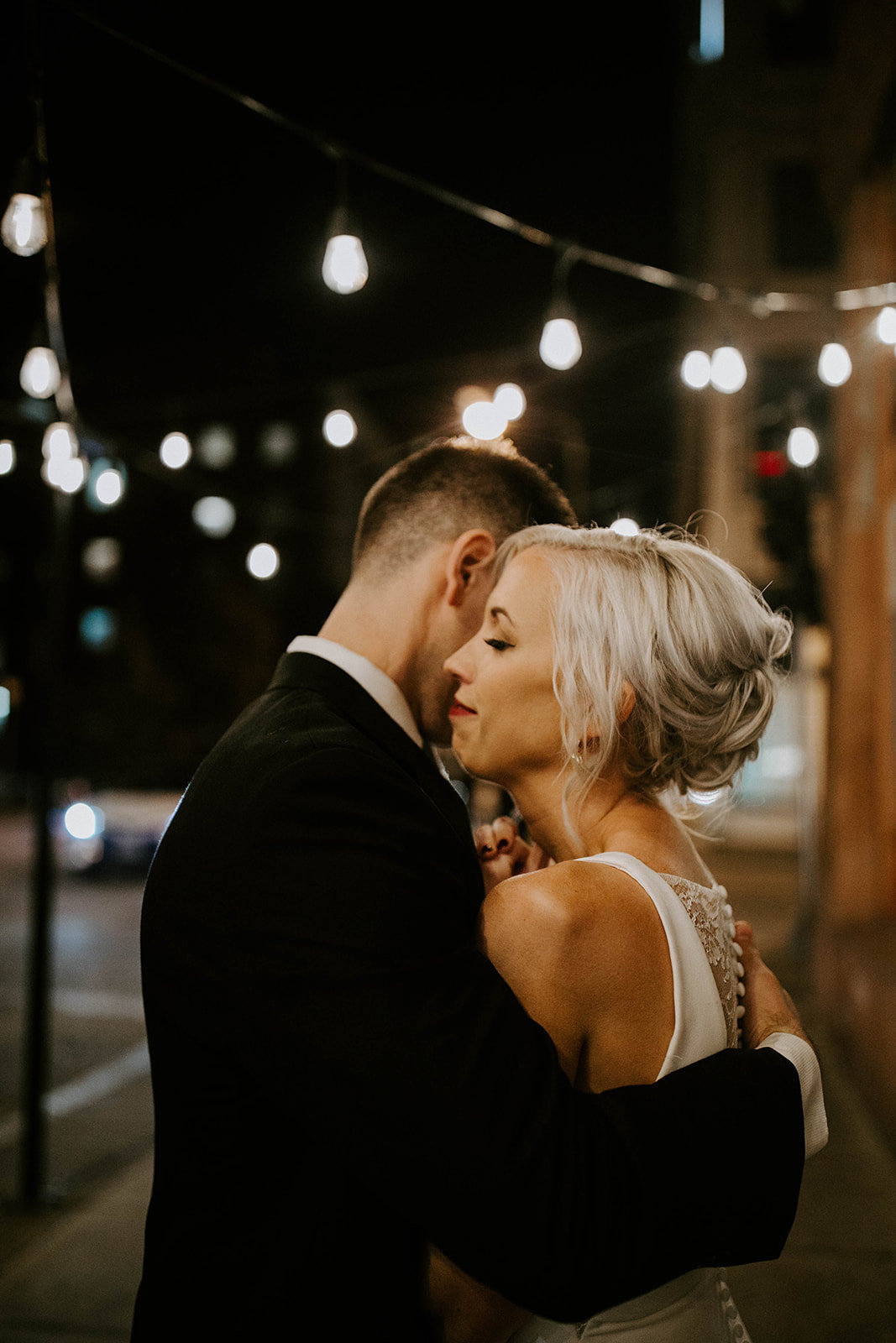 A bride and groom embrace with city lights behind them.
