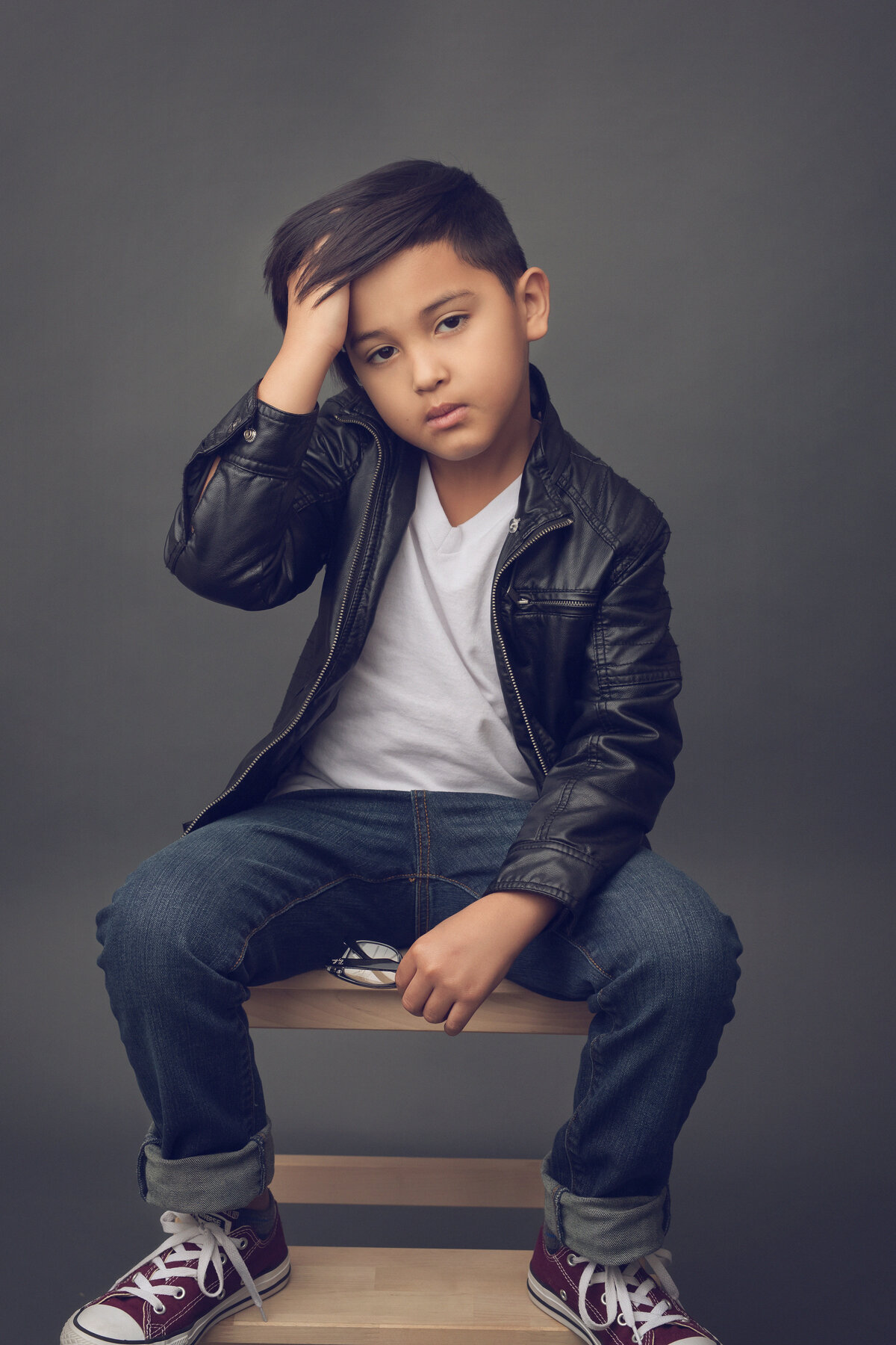 Young boy sitting on a stool, hand in hair, facing the camera. Houston, TX.