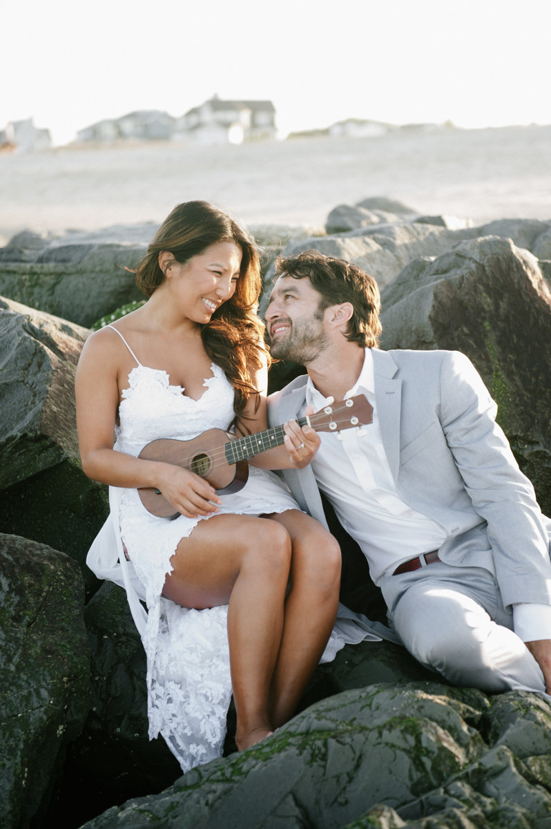 bride playing insturment on beach to groom