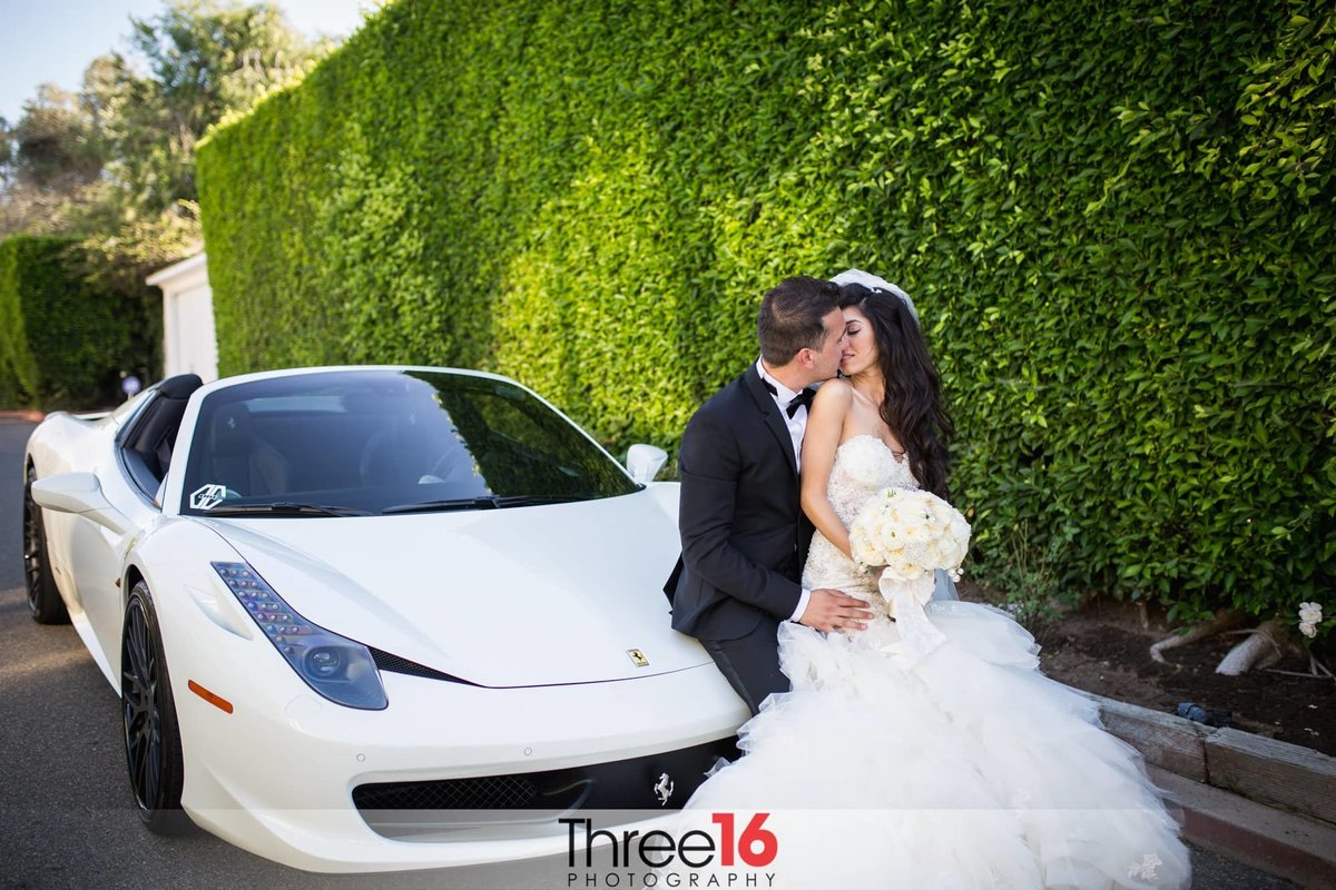 Anticipated kiss between Bride and Groom leaning up against a white car