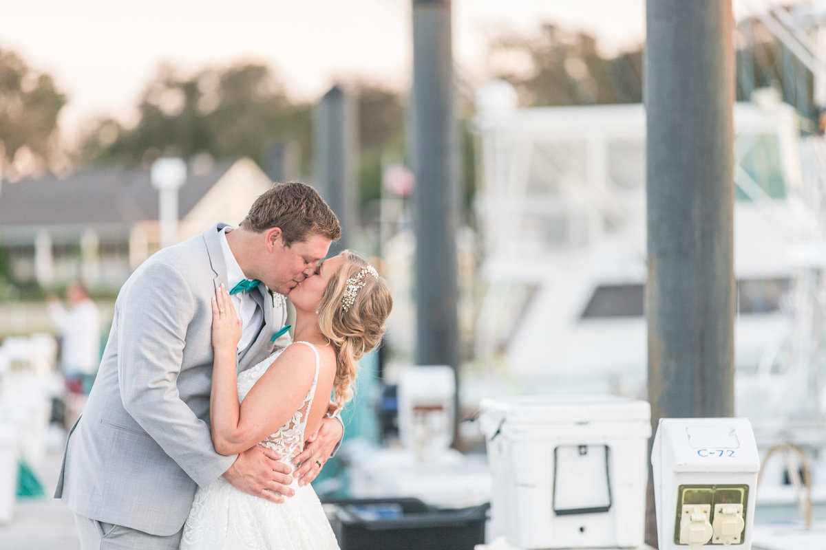 Groom kissing his bride on the docks at The Water Table