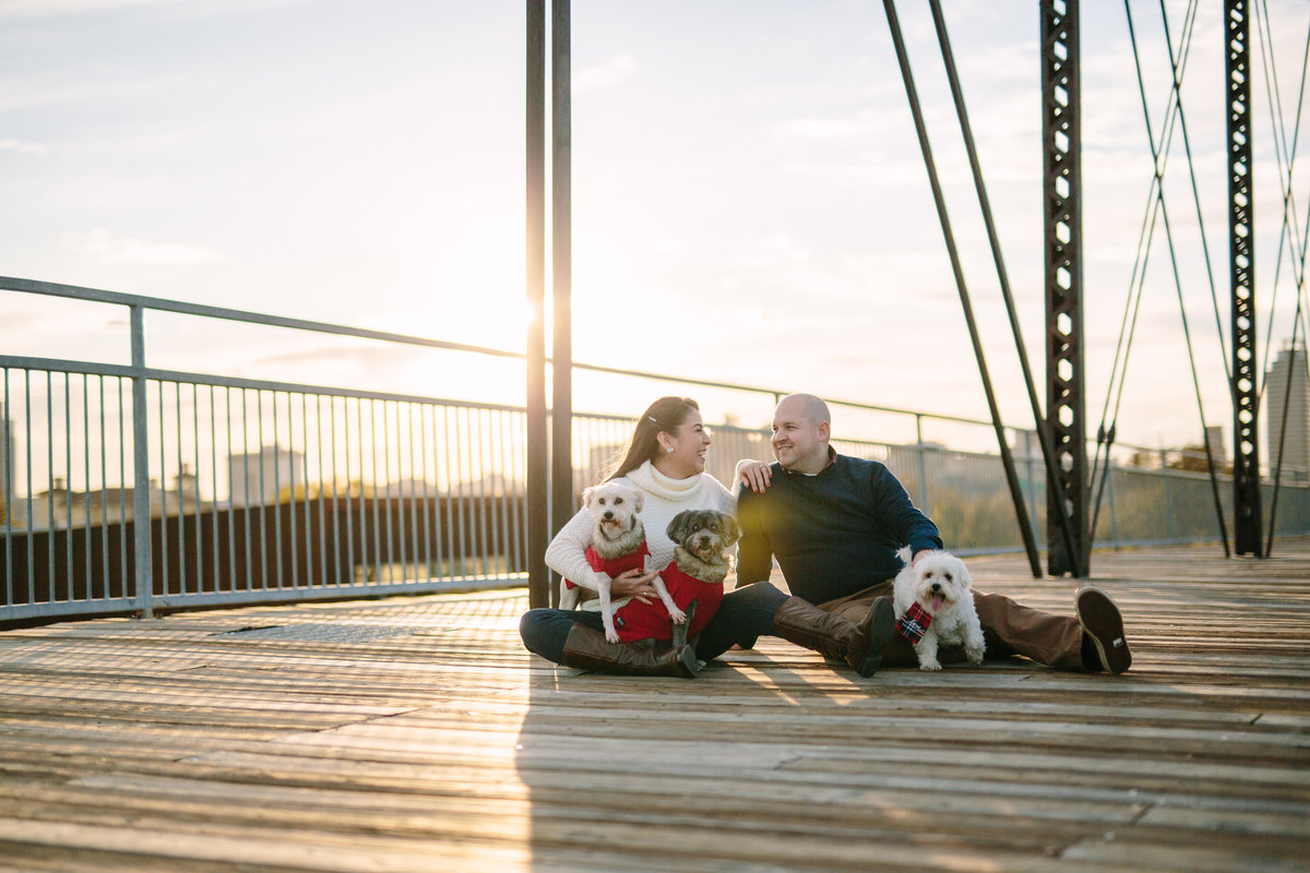 Fiancé and fiancée with their dogs sitting on a bridge in downtown San Antonio at their engagement session.