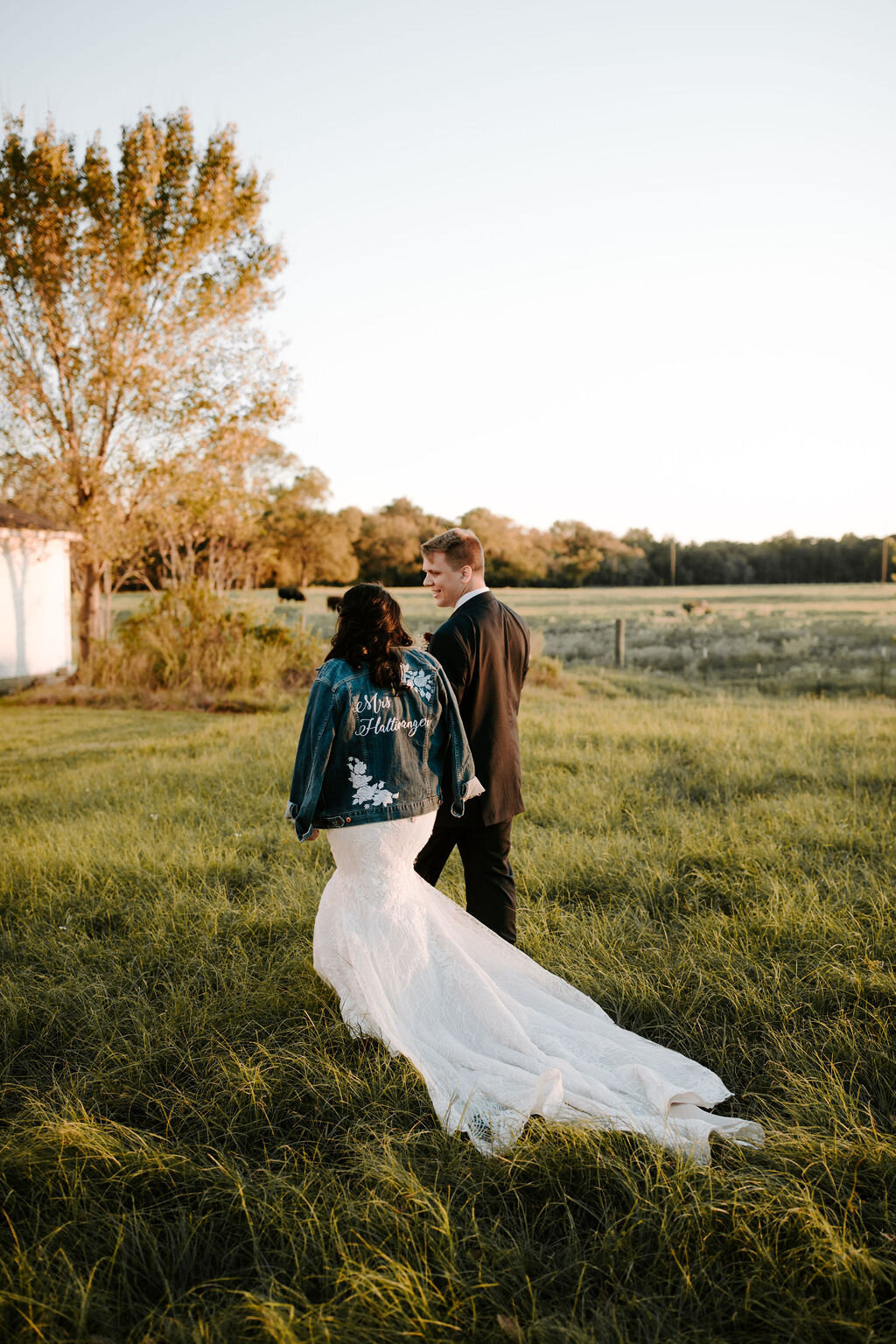 A bride and groom walking through a field at sunset, the bride is wearing a denim jacket with her new last name on it