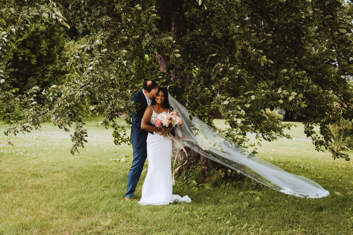 bride with cathedral veil  cuddling with groom underneath a tree at the Arboretum
