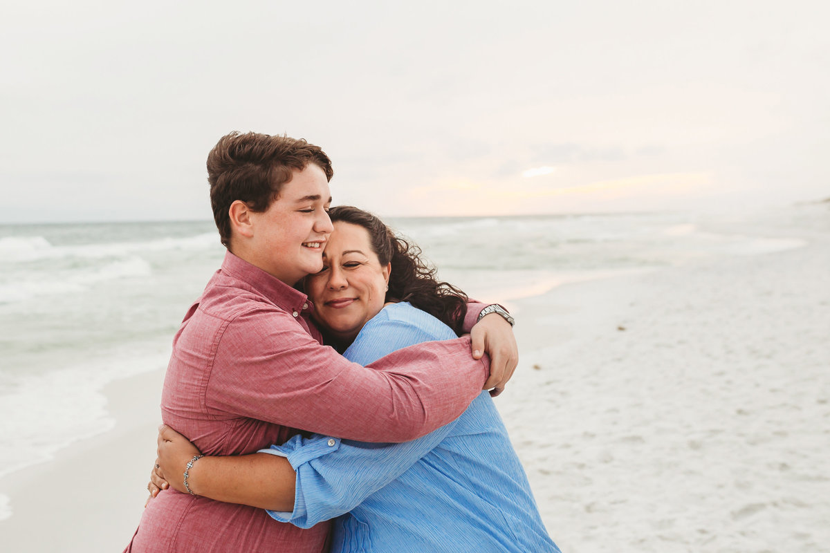 Older son hugging his mother, on the beach