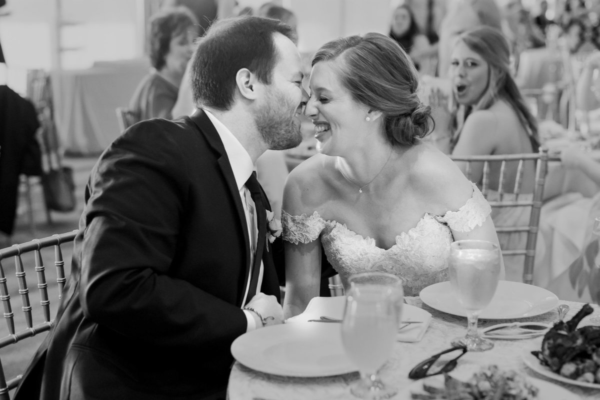 bride and groom laugh during dinner