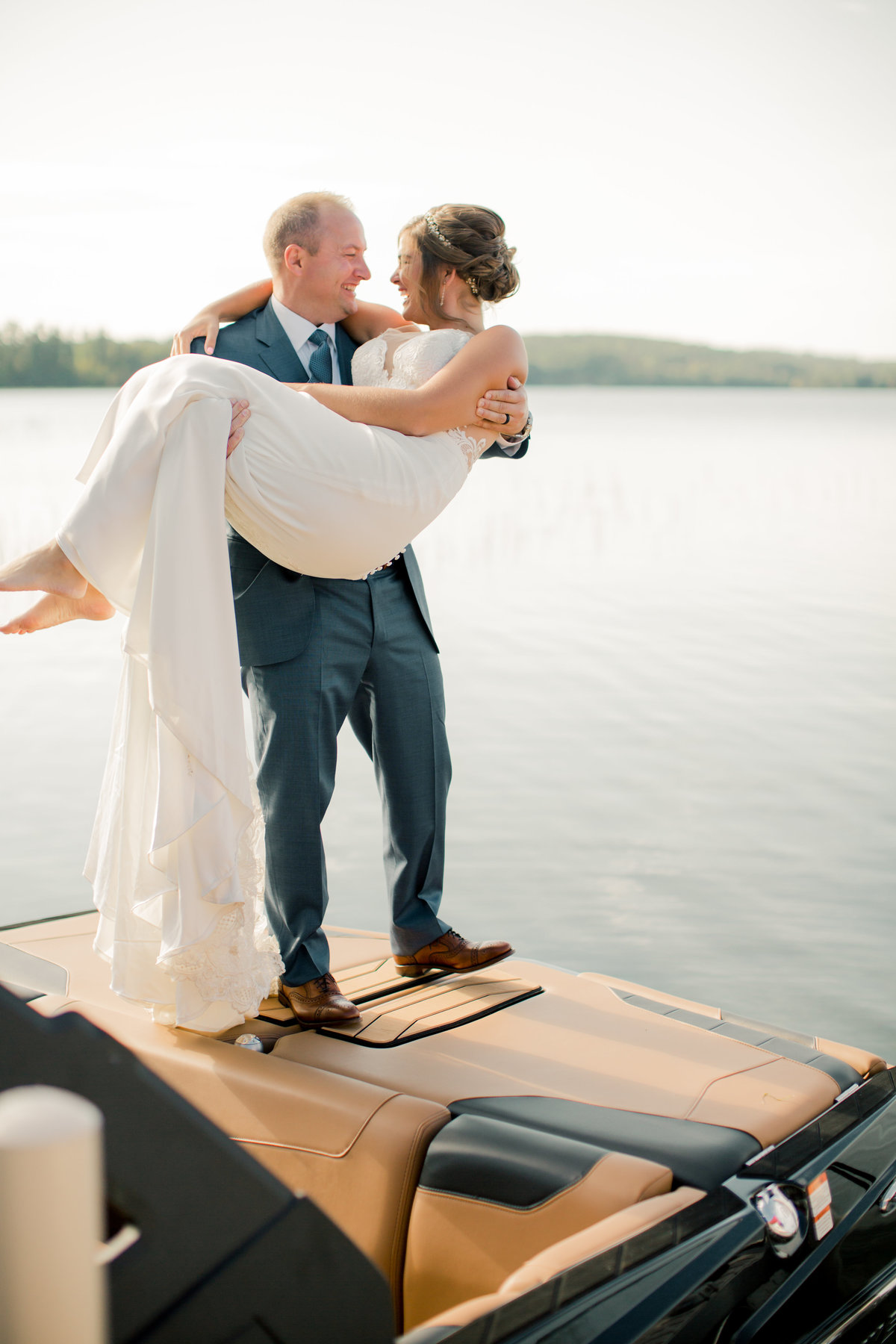 crossing the threshold of the dock to boat carried by new husband gull lake minnesota