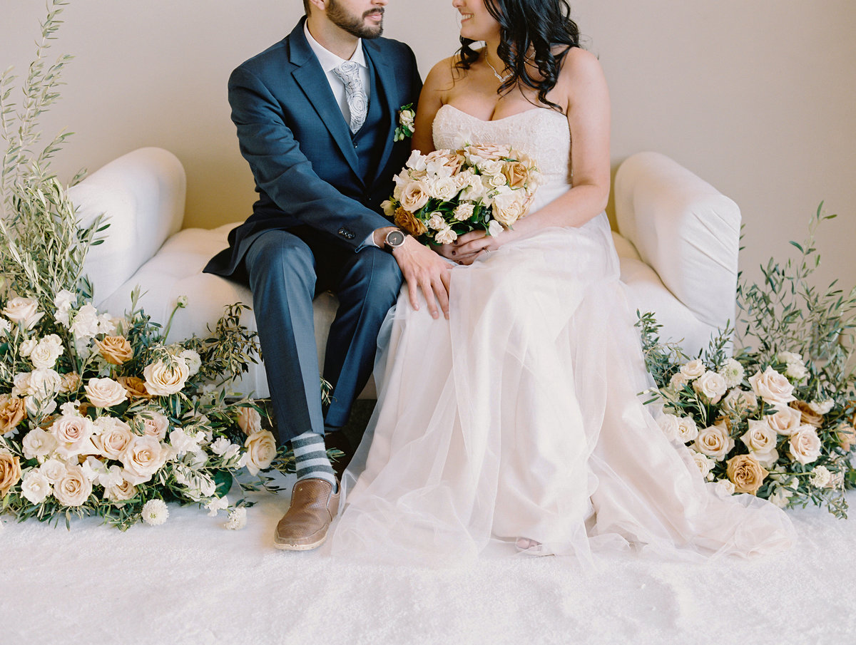 a photo of a bride and groom on a tufted ottoman surrounded by flowers with wild greenery and floral blooms at a wedding at Red Rock Casino in Las Vegas