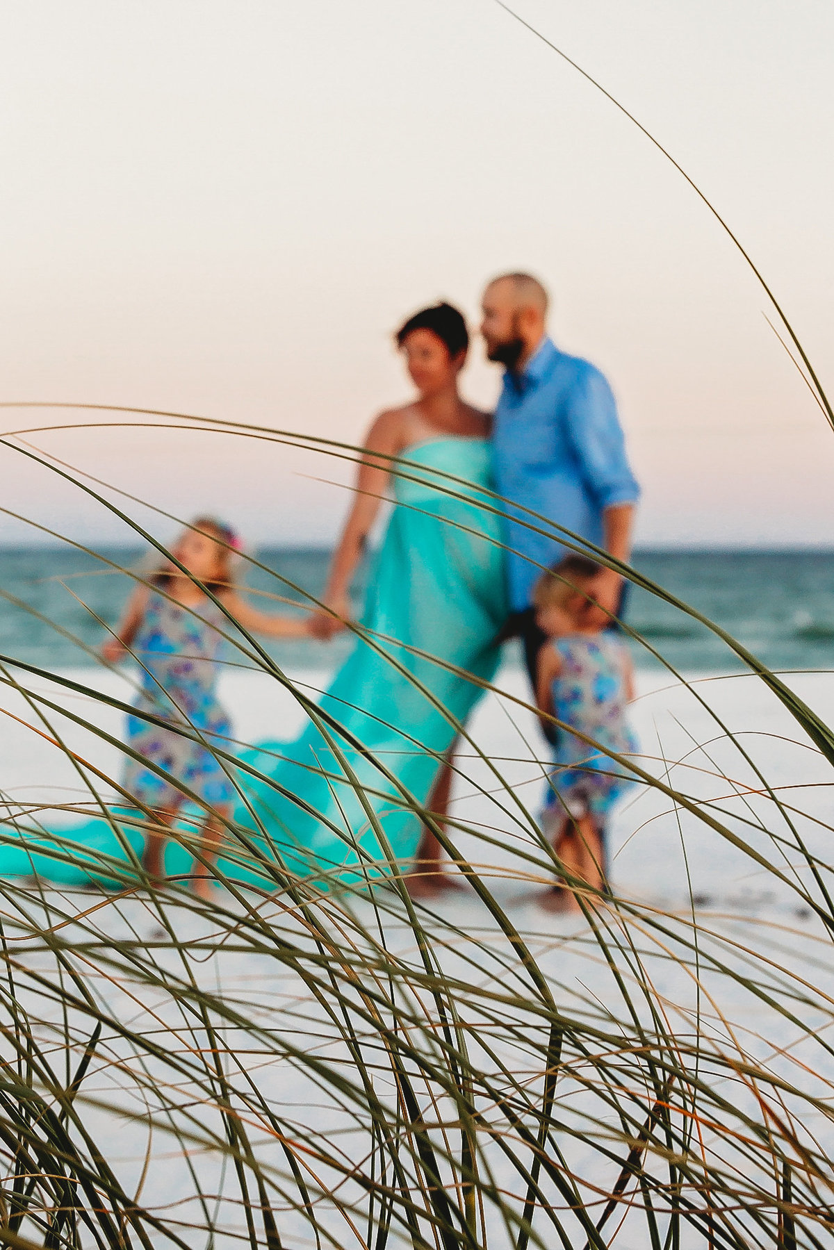Family standing on Navarre Beach for maternity shoot, sea grass