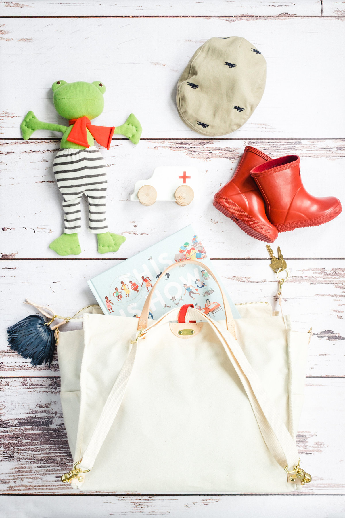 Flat lay image of a Blair Ritchey cream canvas tote bag with children's toys.