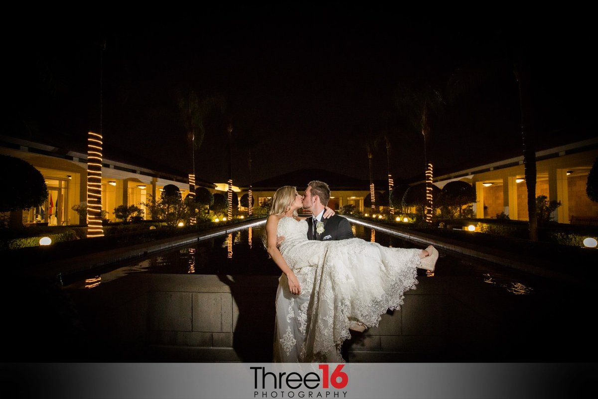 Night shot of the Groom carrying and kissing his Bride next to the reflection pool