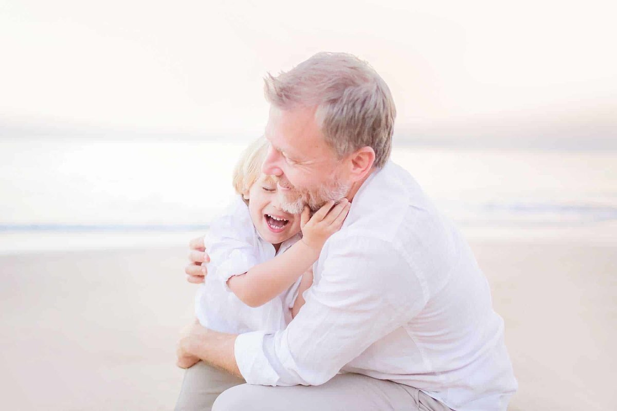 Father hugs his young boy who laughs and smiles during sunrise beach portrait session on Maui