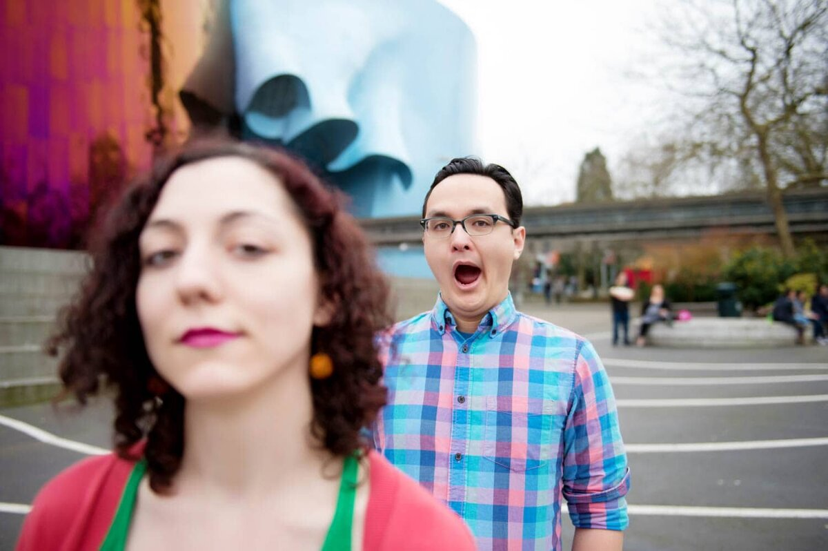 a man in a colorful shirt yawns during engagement session in seattle