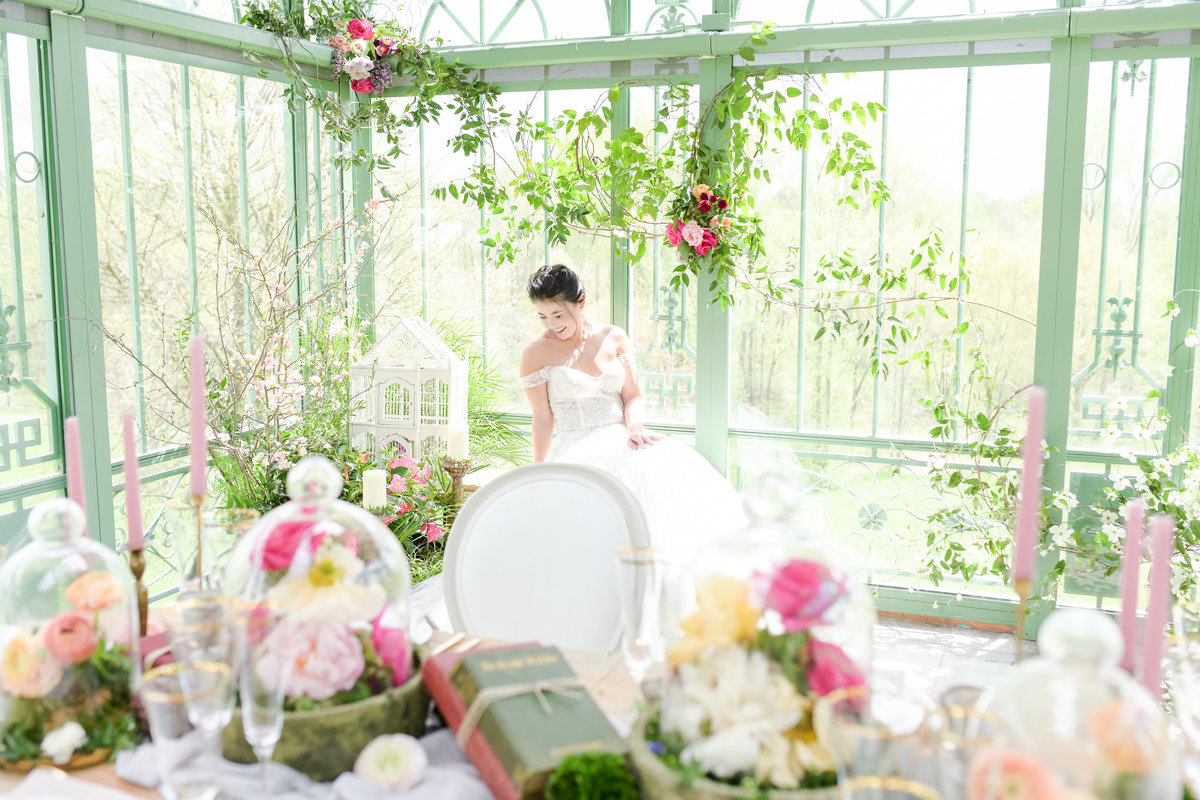 Bride in greenhouse with floor to ceiling windows andfloral designs all around