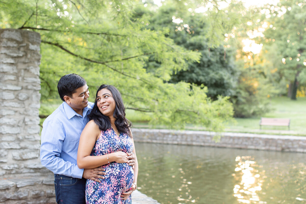 Spring Sunset Maternity Session with maxi dress standing by fountain  at Oak Knoll Park in St. Louis by Amy Britton Photography Photographer  in St. Louis